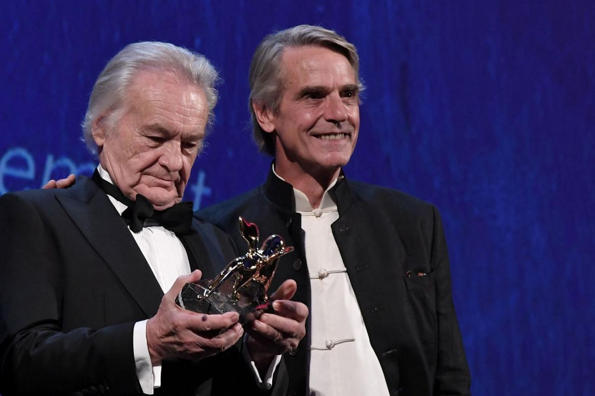 Director Jerzy Skolimowski (left) receives the Golden Lion for Lifetime Achievment from actor Jeremy Iron (right) during the opening ceremony of the 73rd Venice Film Festival, on Aug 31, at Venice Lido.