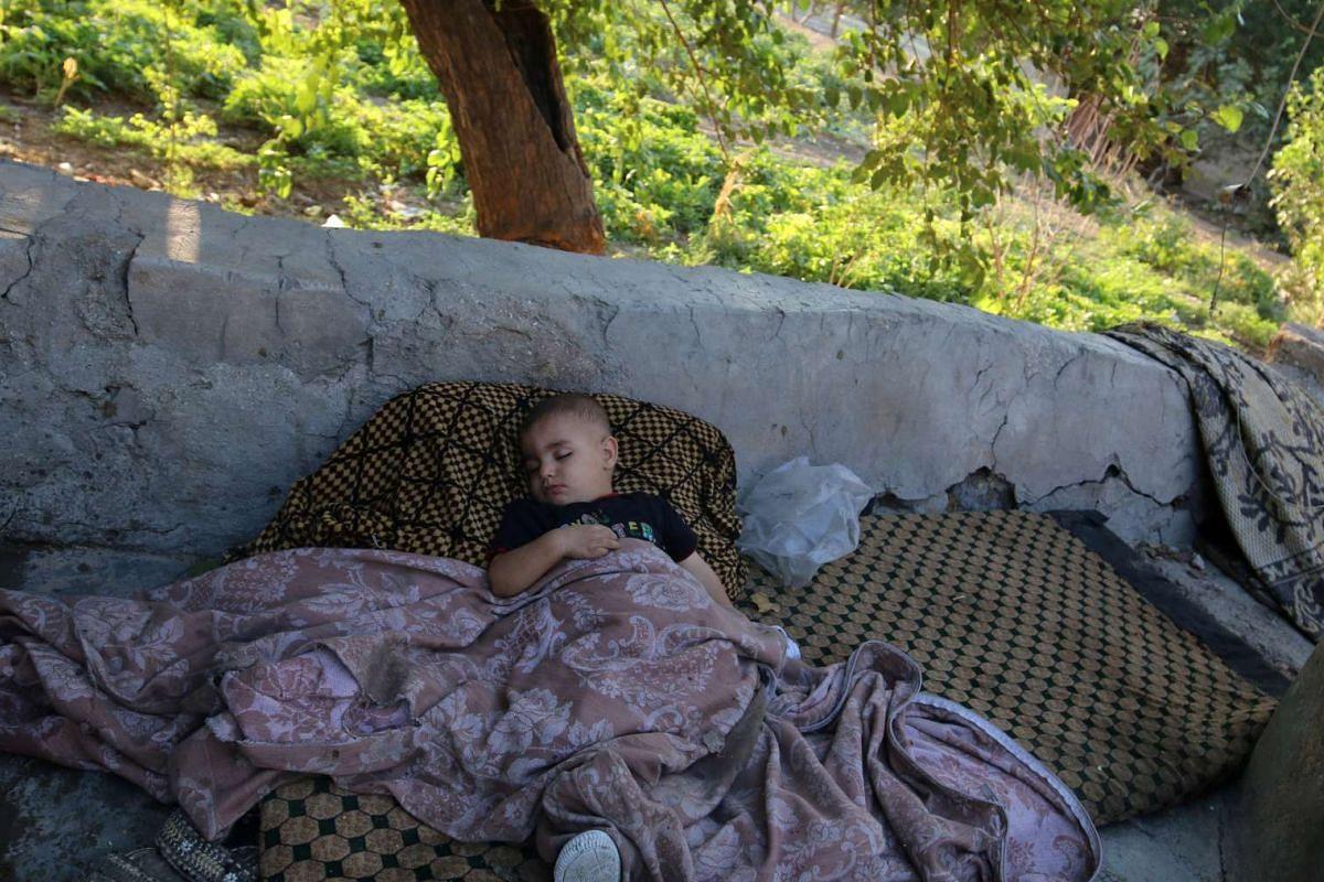 A boy sleeps outdoors in the rebel-held al-Sheikh Said neighbourhood of Aleppo, Syria on Sept 1, 2016.