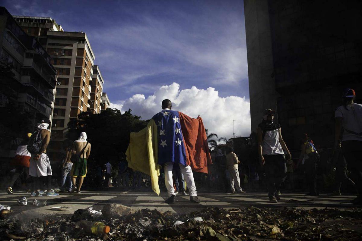 A protester wears a Venezuelan flag in the Altamira neighborhood of Caracas, Venezuela, on Sept 1, 2016.