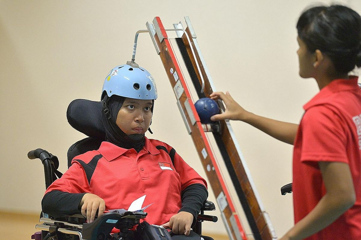 Boccia player Nurulasyiqah Taha (left) lining up a shot in training at OCBC Arena. Her sister Nurulsyahirah Taha, 30, is assisting her. Nurulsyahirah is also in Rio to help her older sibling, 31, execute her shots.