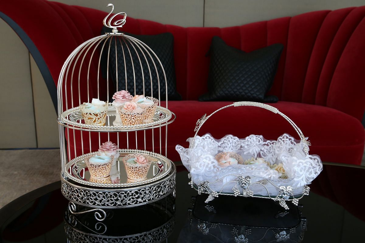 Lovlihaus' stainless-steel birdcage stand ($300) and stainless-steel grapevine tray ($65).