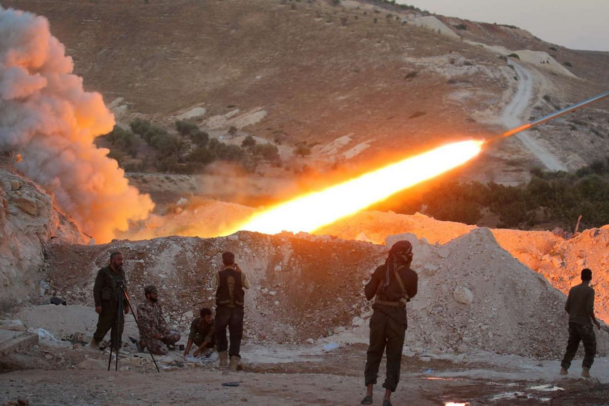 Free Syrian Army fighters launch a Grad rocket from Halfaya town in Hama province, towards forces loyal to Syria's President Bashar al-Assad at the Zein al-Abidin mountain on Sept 4, 2016.