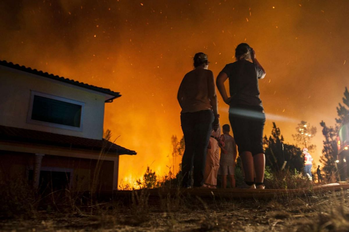 Residents of Fonte Fria village watch the fire near their homes after receiving evacuation order by the authorities, in the district of Leiria, centre of Portugal, September 5, 2016. PHOTO: EPA
