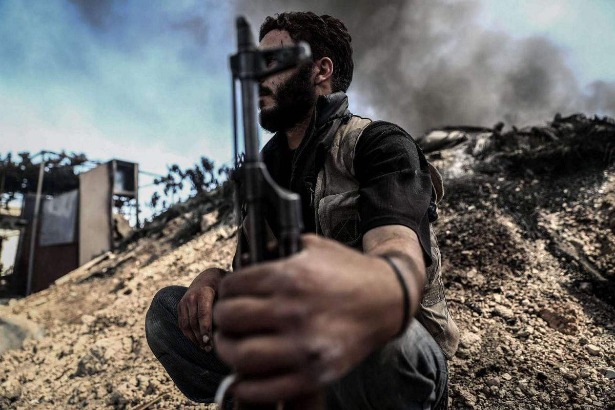 A fighter from the Jaish al-Islam (Islam Army) sits near smoke billowing on the front-line, which they use to take cover, in the village of Tal al-Siwan area of the rebel-held stronghold of Douma, on the outskirts of Damascus, on September 5, 2016. P