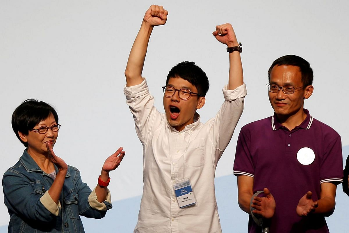 Student leader Nathan Law (centre) celebrates on the podium after his win in the Legislative Council election in Hong Kong, China on Sept 5, 2016.