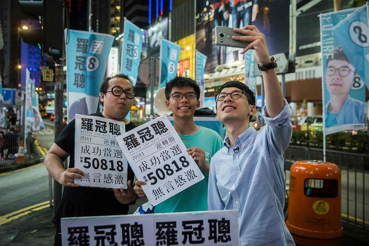 Nathan Law (right) and Joshua Wong (centre) take a selfie at a rally in Causeway bay following Nathan Law's win in the Legislative Council election in Hong Kong on Sept 5, 2016.