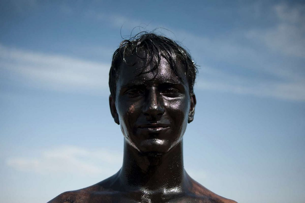 A young man covered in black grease stands during the traditional festivities of the Cascamorras, in Baza, near Granada, on September 6, 2016. PHOTO: AFP