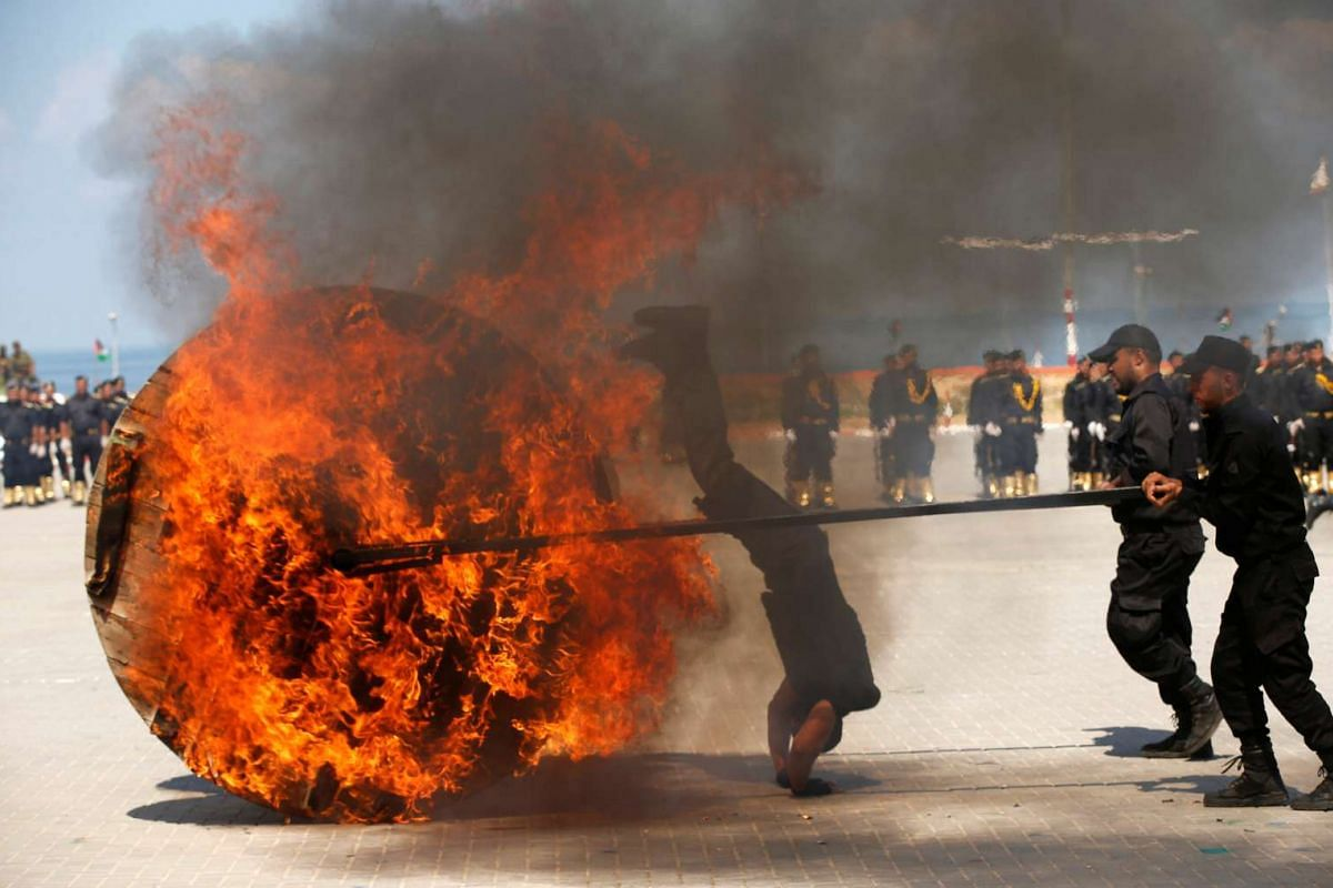 A Palestinian policeman loyal to Hamas jumps over fire during a graduation ceremony in Gaza City September 6, 2016. PHOTO: REUTERS