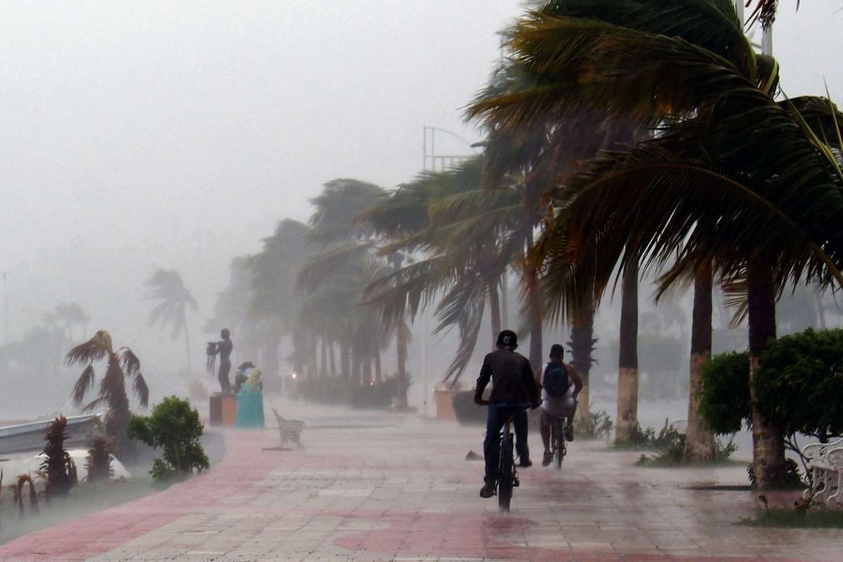 Two men ride bikes along the seaside Boulevard of La Paz during the passage of Hurricane Newton, in Baja California Sur state, Mexico, on September 6, 2016. PHOTO: AFP