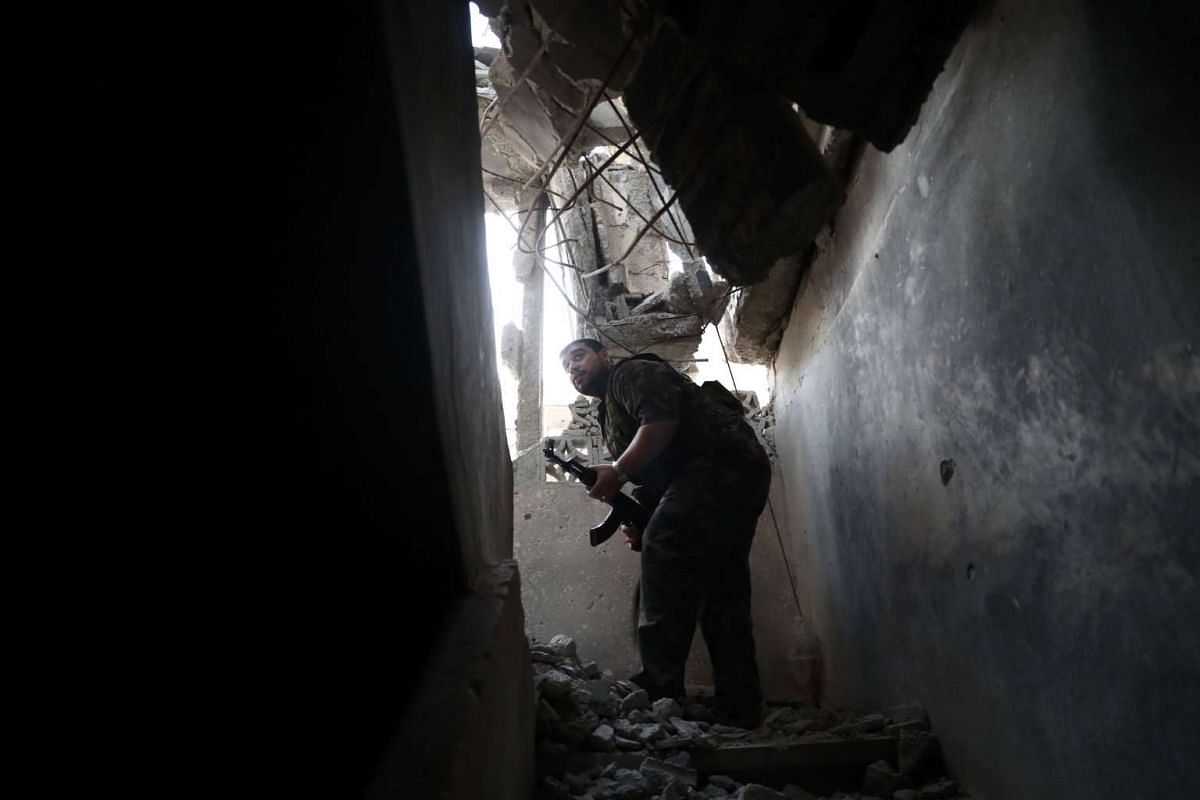 A rebel fighter inspects a damaged building near the front line in the rebel-held neighbourhood of Jobar, on the eastern outskirts of the capital Damascus on September 6, 2016. PHOTO: AFP