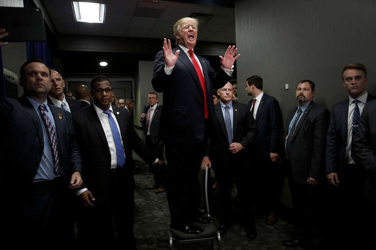 Republican presidential nominee Donald Trump stands on a chair to speak to people in an overflow area after a campaign rally in Greenville, North Carolina, U.S., September 6, 2016. PHOTO: REUTERS