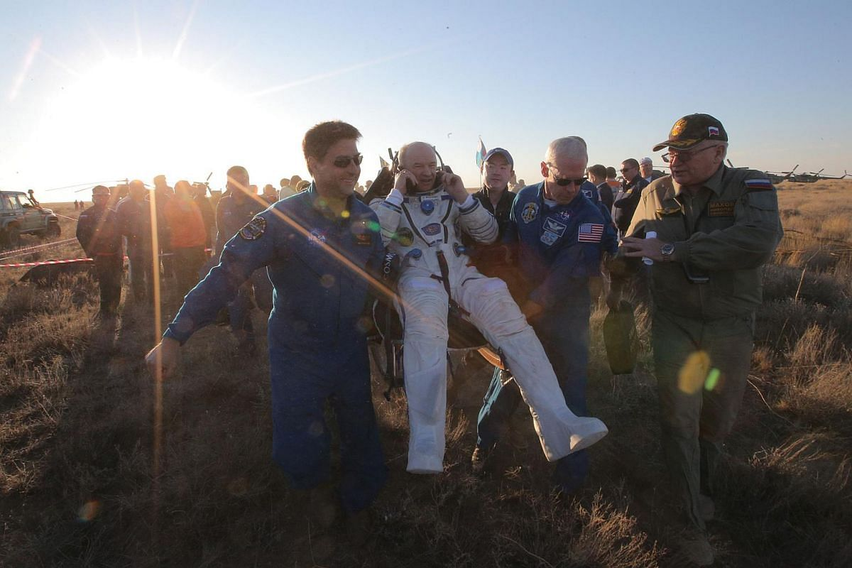 US Nasa astronaut Jeffrey Williams (centre) speaks on a sat phone after landing in Kazakhstan on Sept 7, 2016.