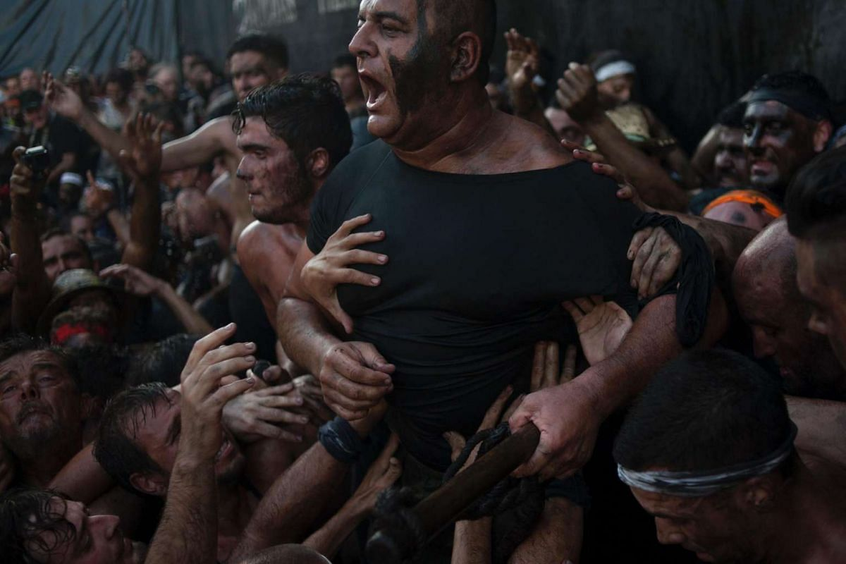 People covered in black grease climb on top of each other during the traditional festivities of the Cascamorras, in Baza, near Granada, on Sept 6, 2016.