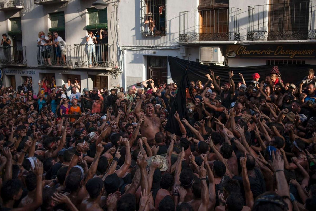 People covered with black grease celebrate the traditional festivities of the Cascamorras, in Baza, near Granada, on Sept 6, 2016.