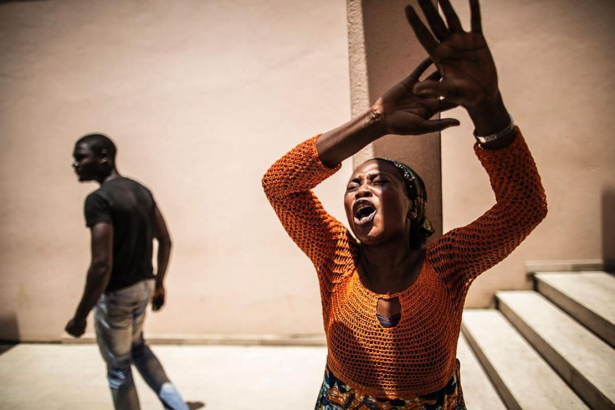 A distressed Gabonese woman reacts at the Libreville Magistrate Court on Sept 6, while she waits, with other relatives, to hear about the release of young men arrested during a wave of unrest that followed the announcement of the results of the Presi