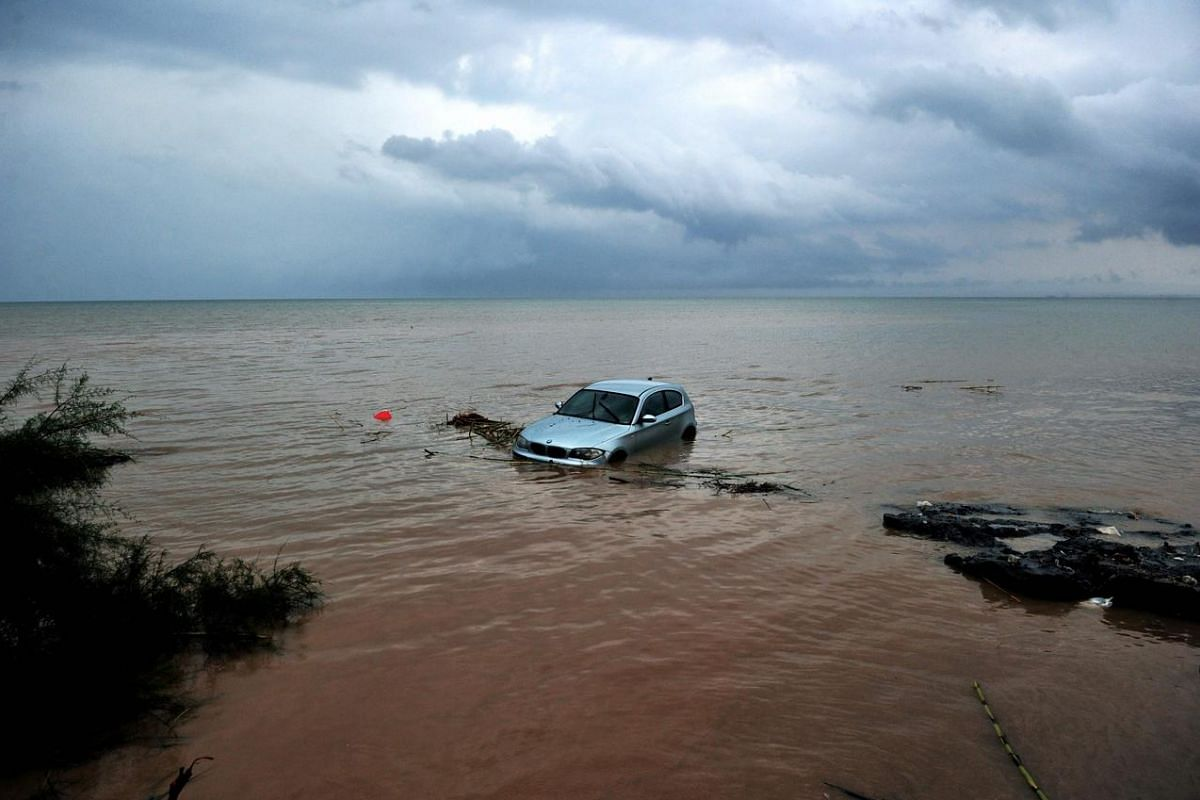 A car washed away into the sea is pictured following floods caused by heavy overnight rain, on Sept 7, in Agia Triada, a suburb of Thessaloniki.