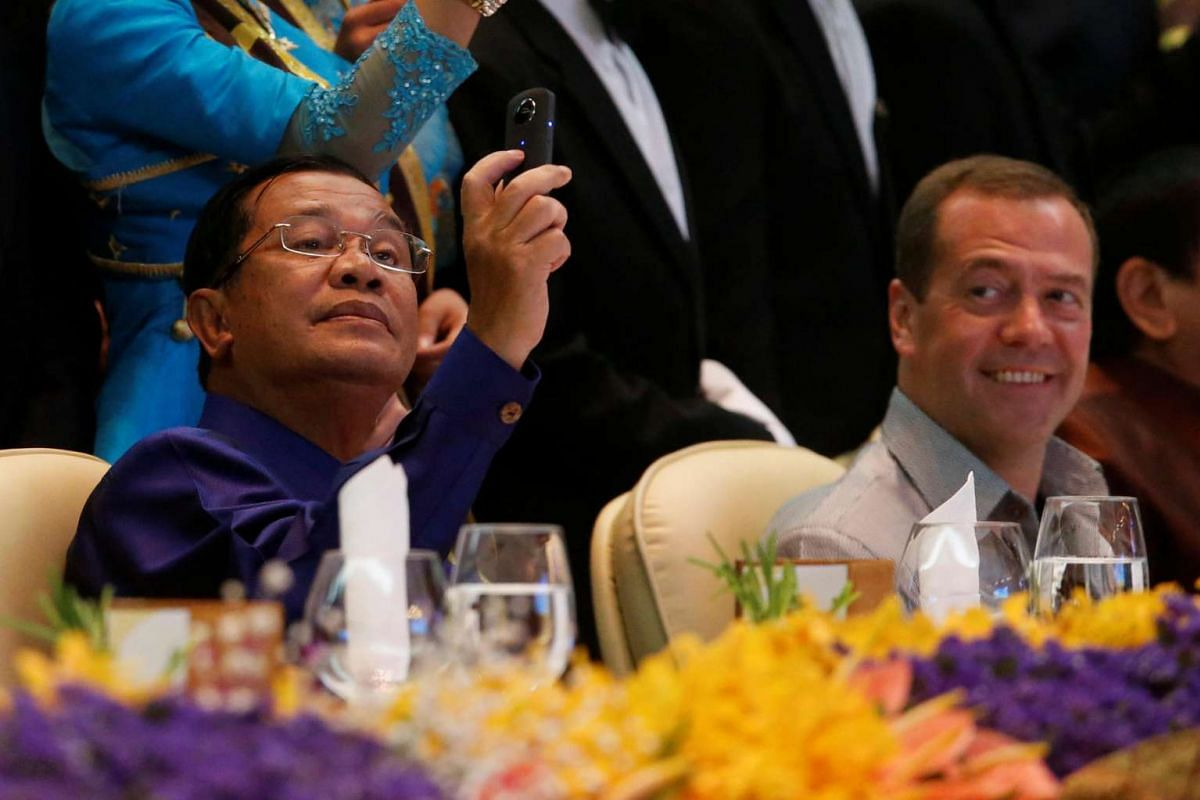 Cambodia's Prime Minister Hun Sen takes a picture while Russia's Prime Minister Dmitry Medvedev looks on during the gala dinner of the 28th and 29th Asean Summits at the National Convention Centre in Vientiane, Laos, on Sept 7, 2016.