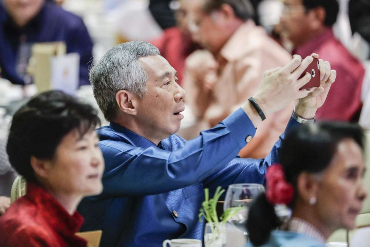 Singapore's Prime Minister Lee Hsien Loong takes pictures with his mobile phone as South Korea's President Park Geun Hye (left) and Myanmar's State Counsellor Aung San Suu Kyi watch the show during dinner.