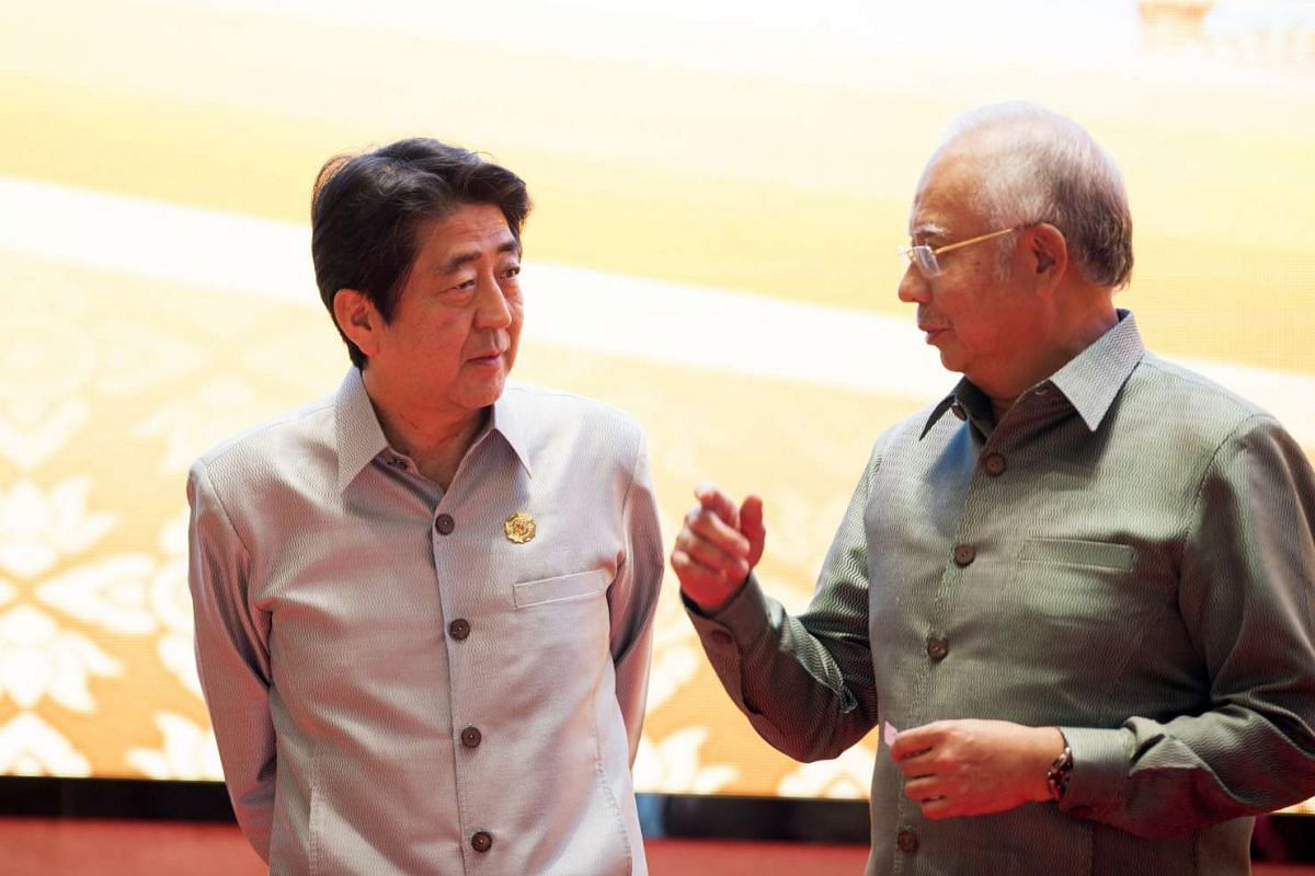 Japanese Prime Minister Shinzo Abe (left) chats with Malaysia's Prime Minister Najib Razak during the gala dinner at the 28th and 29th Asean Summits at the National Convention Centre in Vientiane, Laos, on Sept 7, 2016.