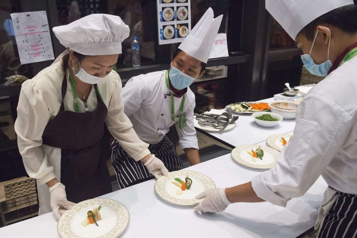 Kitchen staff prepare food before the gala dinner of the 28th and 29th Asean Summits at the National Convention Centre in Vientiane, Laos, on Sept 7, 2016.