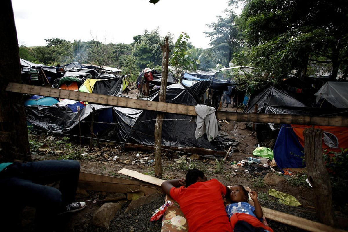 An African migrant stranded in Costa Rica rests with his child at camp at the border between Costa Rica and Nicaragua, in Penas Blancas, Costa Rica, Sept 7.