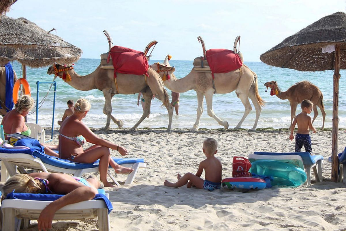 Tourists relax on a beach on the island of Djerba, Tunisia, on Sept 7.