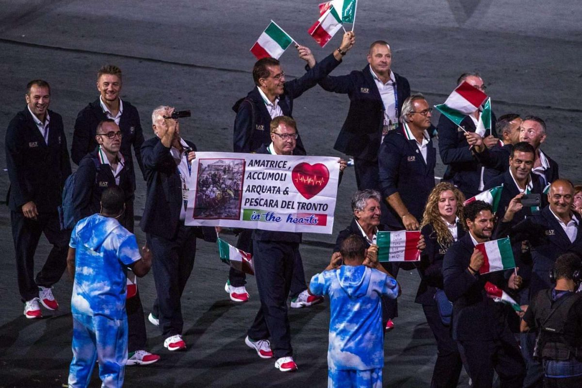 A member of the Italian delegation holds a banner displaying the names of the towns affected by the Sept 3 earthquake in central Italy during the opening ceremony of the Rio 2016 Paralympic Games at the Maracana Stadium in Rio de Janeiro, Brazil, on