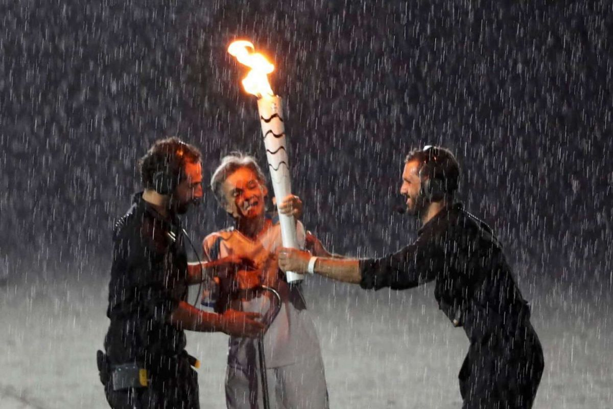Brazilian Paralympic runner Marcia Malsar is assisted after falling while carrying the torch as rain falls during the opening ceremony of the Rio 2016 Paralympic Games at the Maracana Stadium in Rio de Janeiro, Brazil, on Sept 7, 2016.