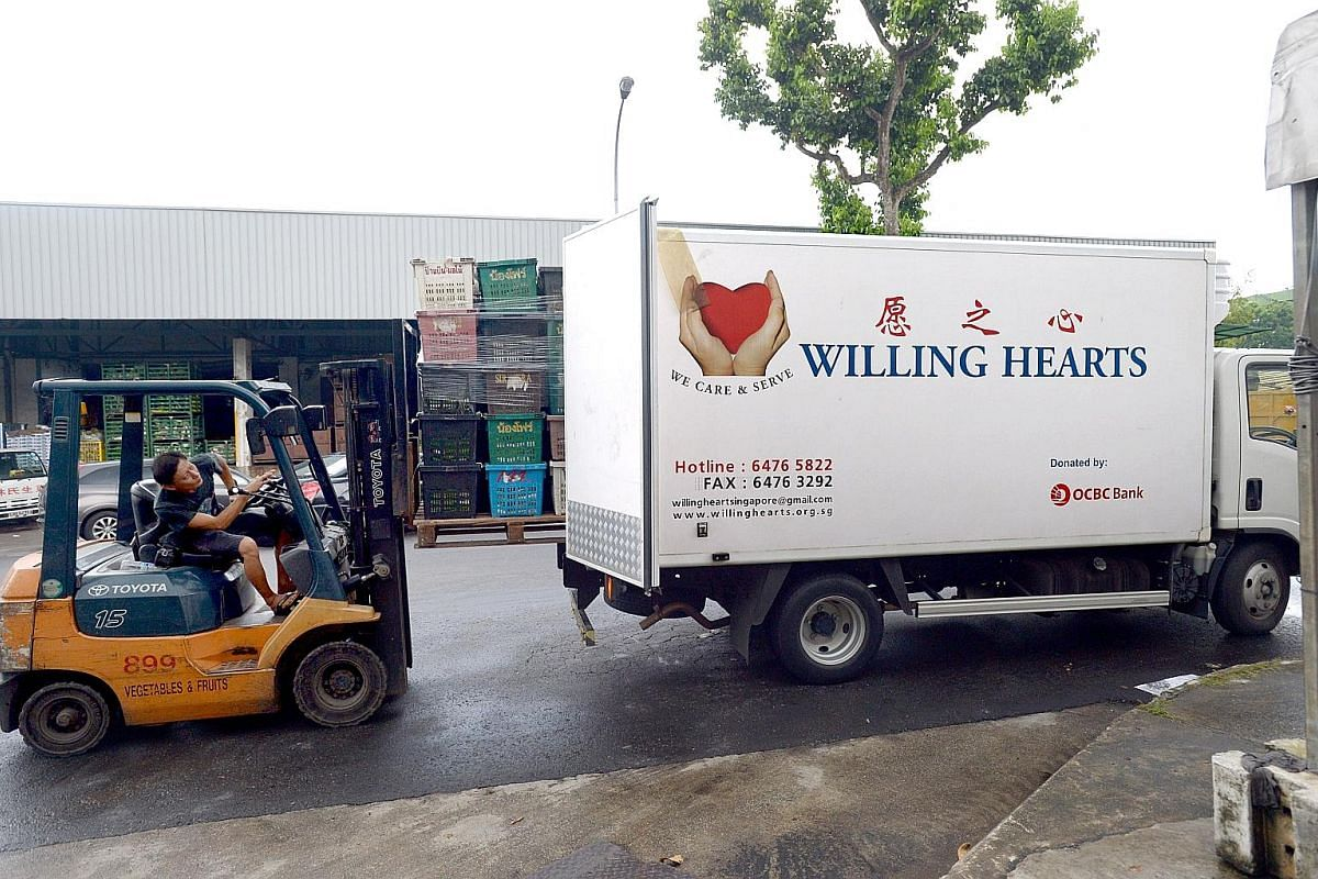 Vegetable importer Lim Hiok Chuan, 65, hands out sacks of potatoes to an employee of Willing Hearts at the Pasir Panjang Wholesale Centre. Mr Lim, who has been giving his products to Willing Hearts regularly for the last 10 years, has never turned do