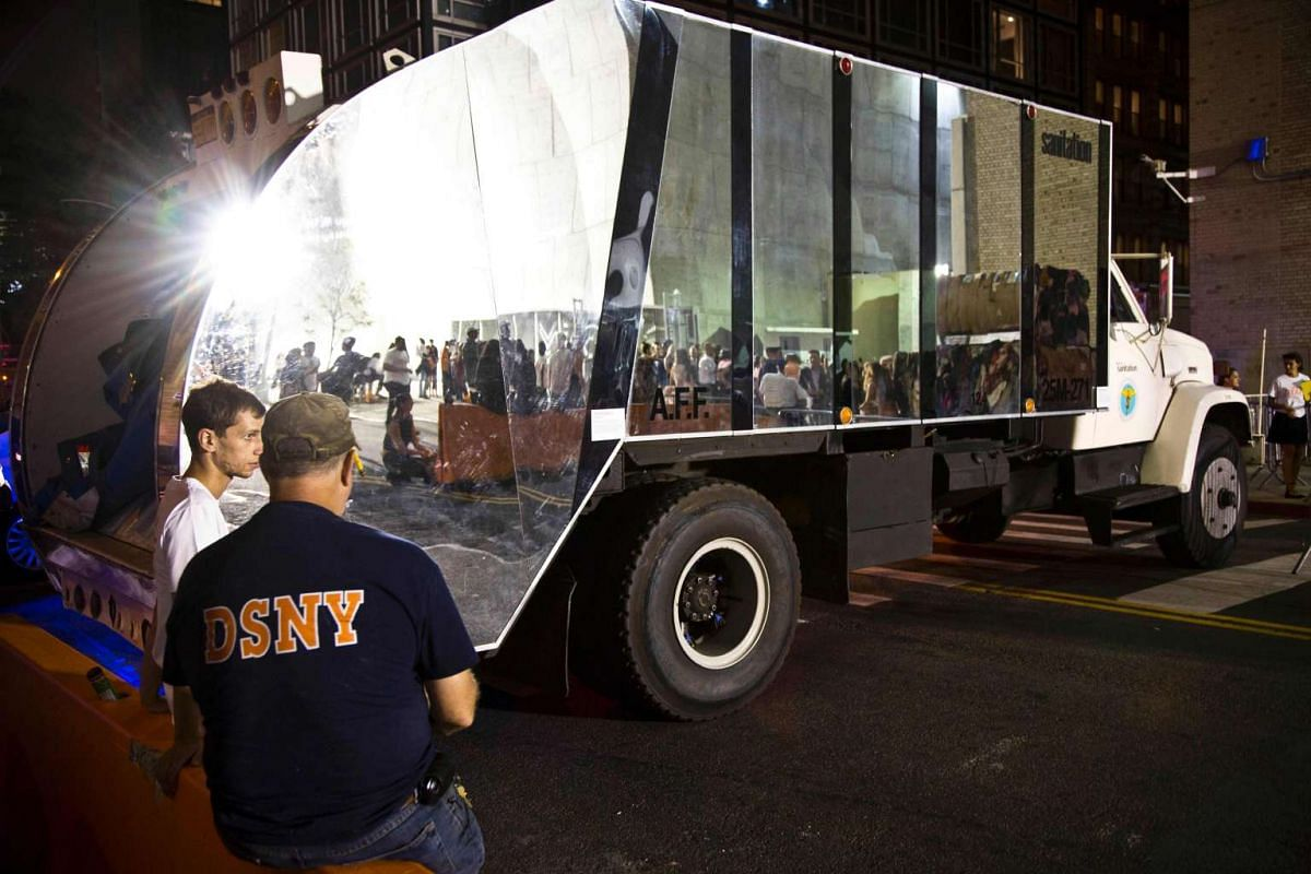 A shiny garbage truck reflects the Sanitation Department themed Heron Preston DSNY Uniform presentation during New York Fashion Week on Sept 7, 2016.