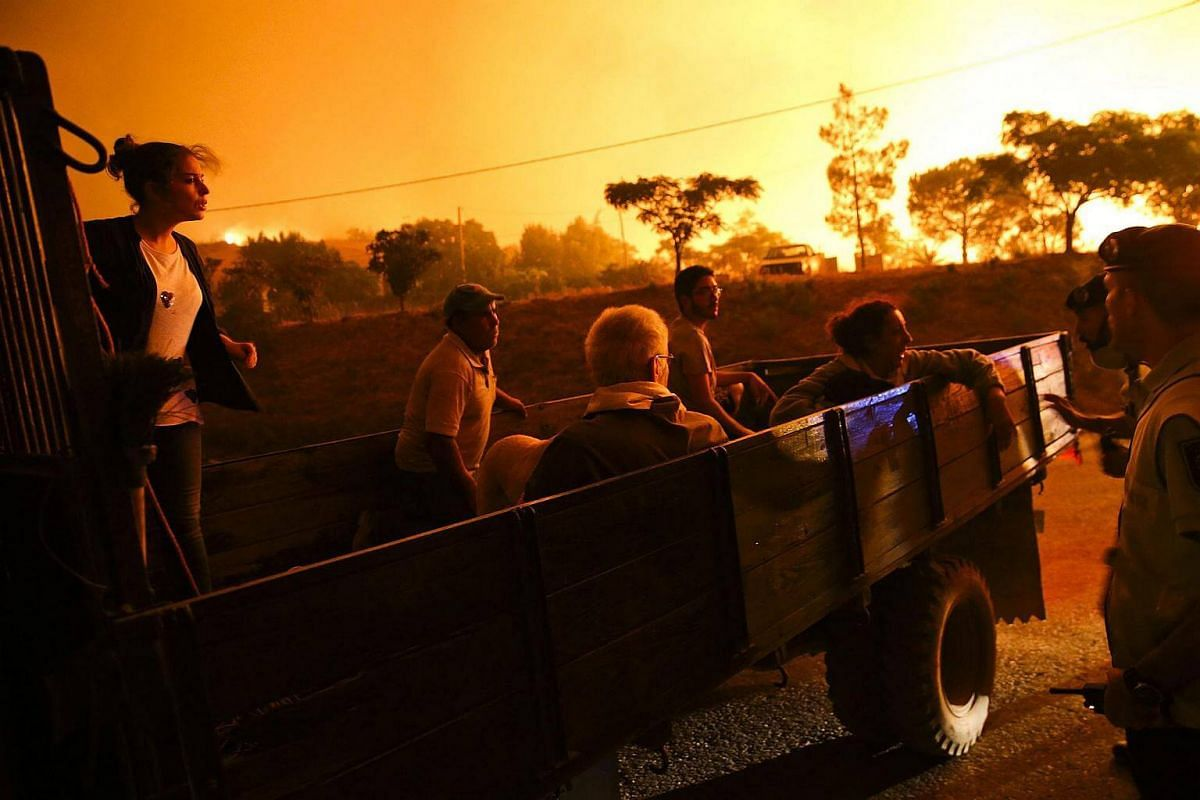 People are carried in the back of a truck after being evacuated from their home due to a forest fire in the area of Serra de Monchique, in Monchique, Portugal, on Sept 9, 2016.