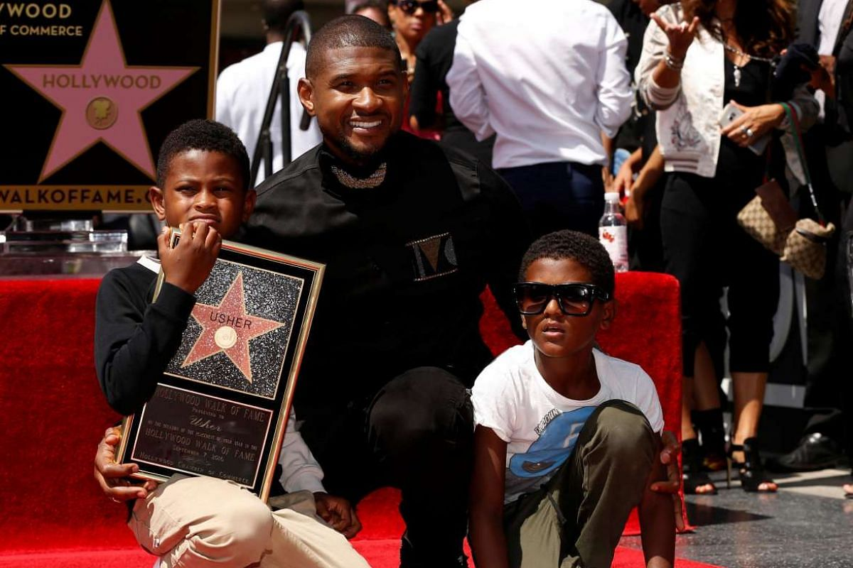 Recording artist Usher poses with his sons Usher Terry Raymond V (left) and Naviyd Ely Raymond after unveiling his star on the Hollywood Walk of Fame in Los Angeles on Sept 7, 2016.
