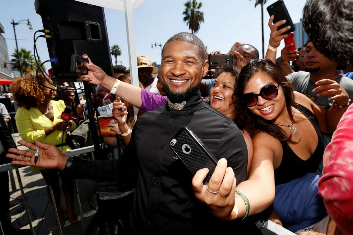 Recording artist Usher poses with fans after unveiling his star on the Hollywood Walk of Fame in Los Angeles on Sept 7, 2016.