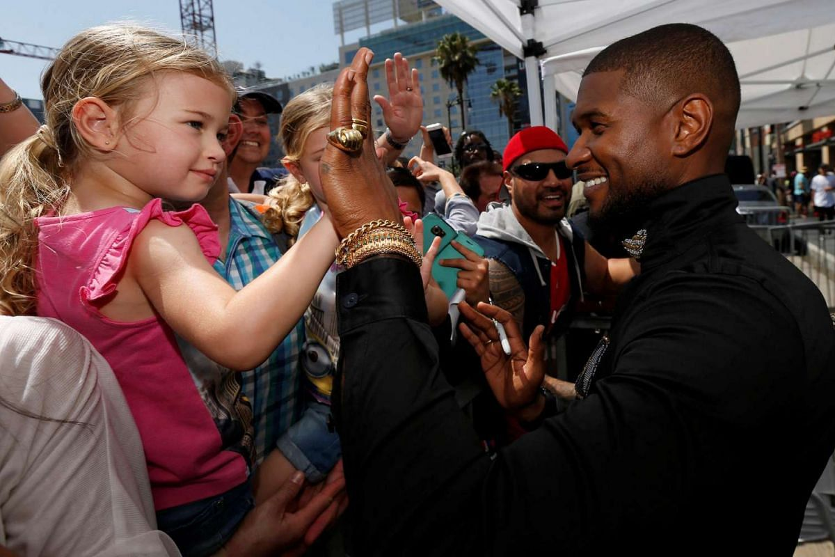 Recording artist Usher gives a high-five to a young girl after unveiling his star on the Hollywood Walk of Fame in Los Angeles, California, on Sept 7, 2016.