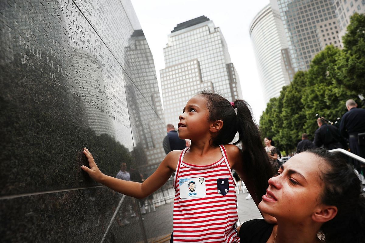 Bernadette Ortiz holds up her daughter Adriana as she looks for the name of her grandfather at a wall commemorating fallen officers, on Sept 9, 2016 in New York City. New York City Police Detective Edwin Ortiz died from illnesses he contracted from i