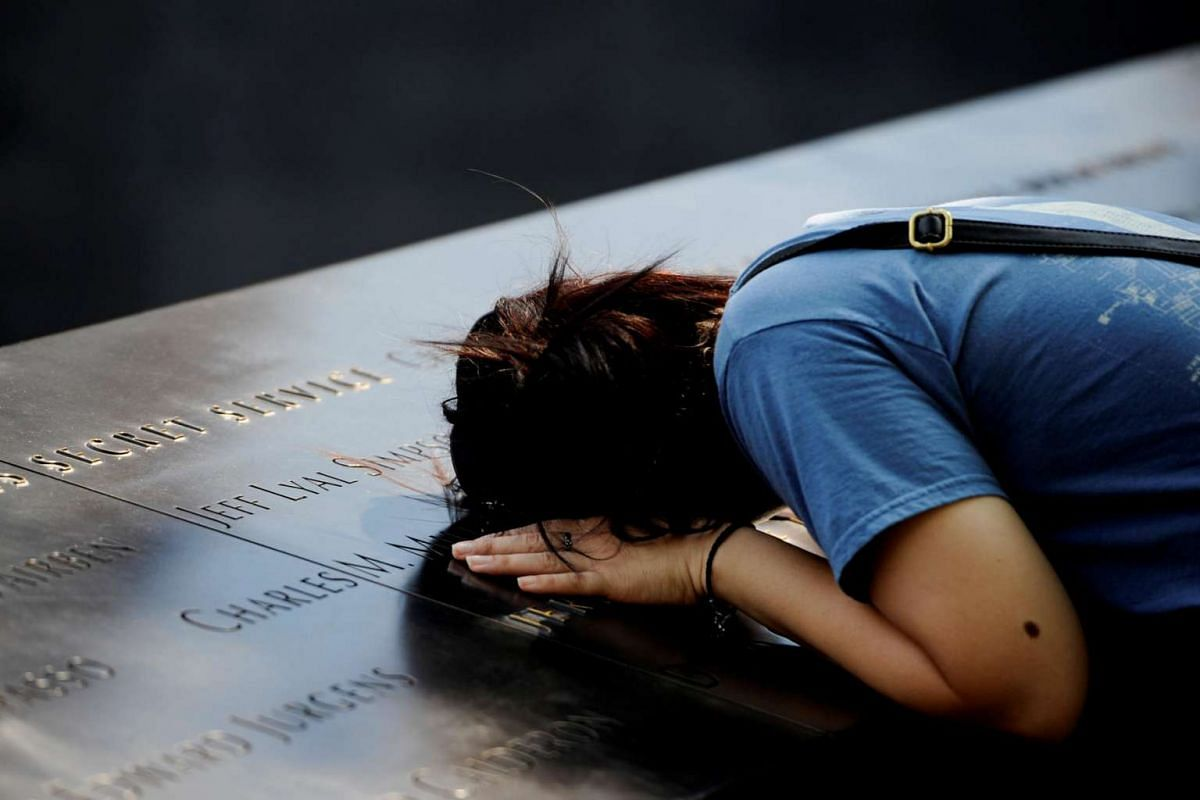 A woman lays her head on a row of names at the National September 11 Memorial, ahead of the 15th anniversary of the attacks in Manhattan, New York, on Sept 10, 2016.