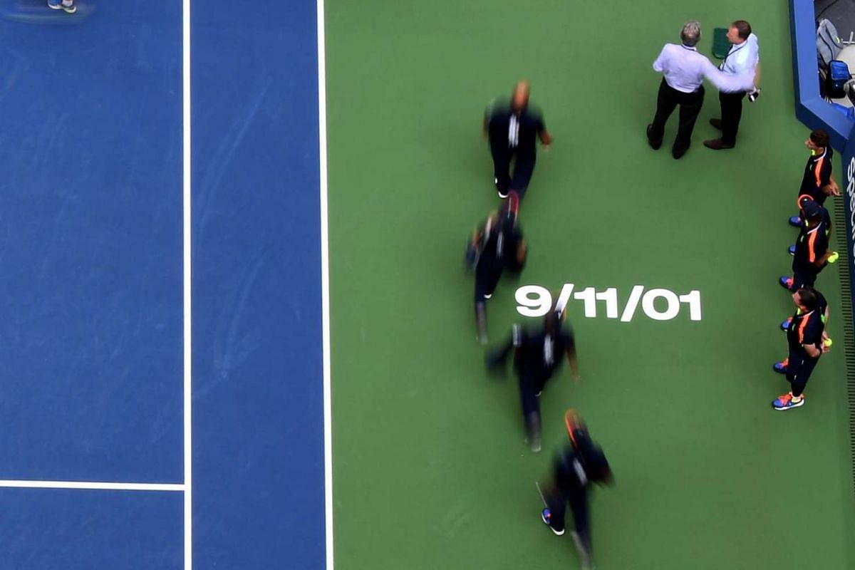 """A """"9/11/01"""" sign stencilled on the Arthur Ashe Stadium court, as match officials arrive before the start of the 2016 US Open Men's Doubles final match on Sept 10, 2016."""