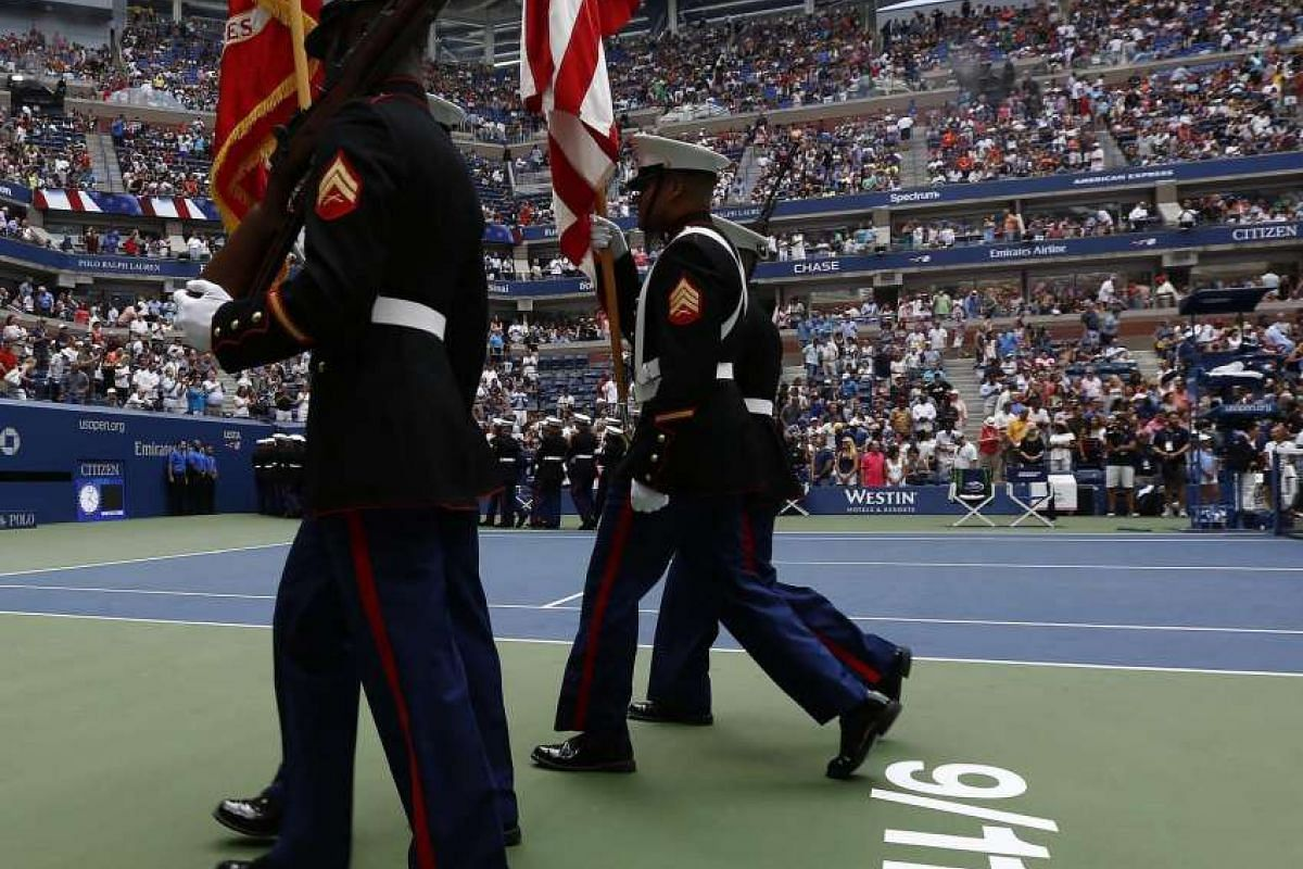 A color guard marches past a stencilled 9/11/01 logo on center court before the women's final at the US Open Tennis Championships at the USTA National Tennis Center in New York, on Sept 10, 2016.