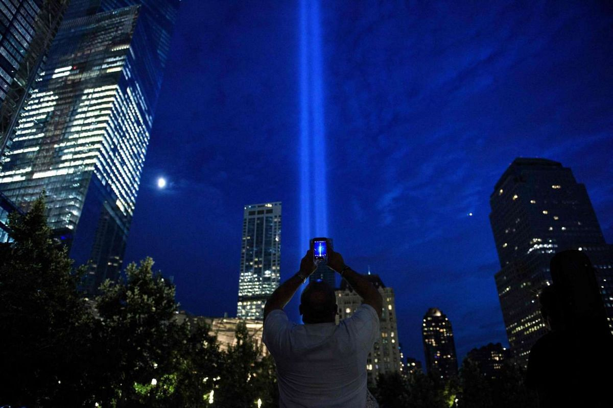 A man photographs beams of light symbolizing the two World Trade Center towers the night before the 15th anniversary of the September 11 attacks, on Sept 10, 2016.