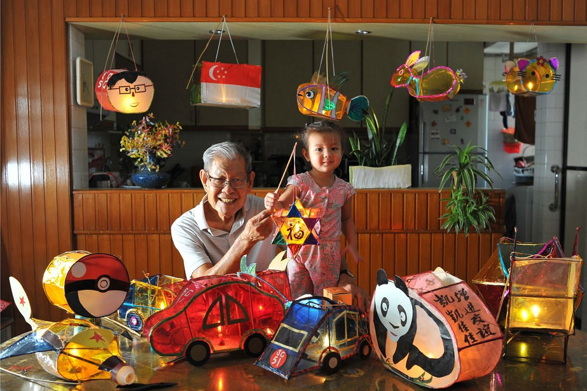 Two-year-old Charlotte Lim-Zagrodnik holding a lantern made by her great-grandfather, Mr Lim Choon Kiang. Around them are more of his lanterns.