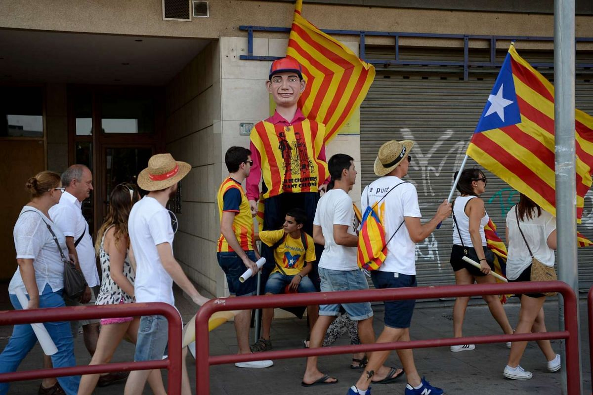 A boy sits next to a giant puppet as people wave Estaladas (pro-independence Catalan flags) during a pro-independence demonstration, on Sept 11, 2016, in Barcelona during the National Day of Catalonia.