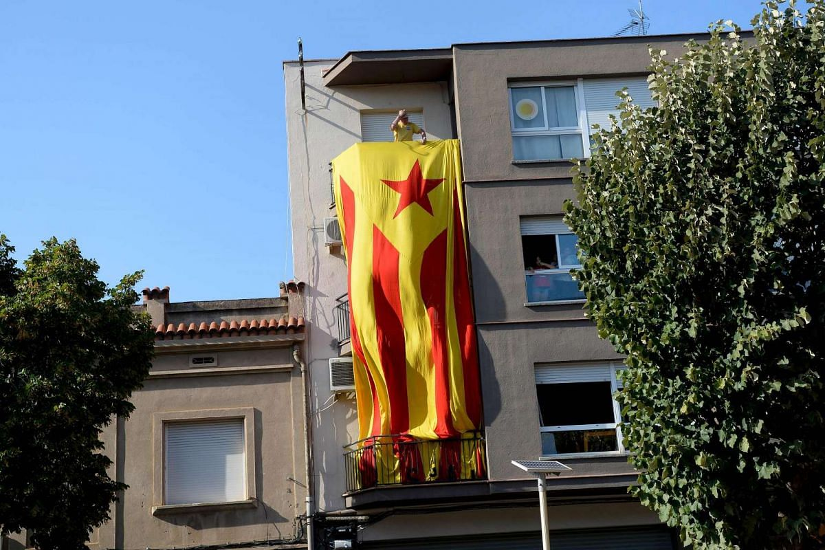 A man unfolds a big Estalada (pro-independence Catalan flag) from his balcony before the start of a pro-independence demonstration, on Sept 11, 2016, in Barcelona during the National Day of Catalonia.