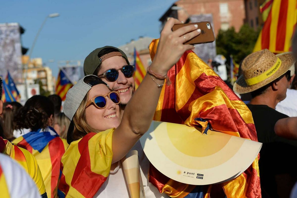 Two people take a selfie photo during a pro-independence demonstration, on Sept 11, 2016, in Barcelona during the National Day of Catalonia.