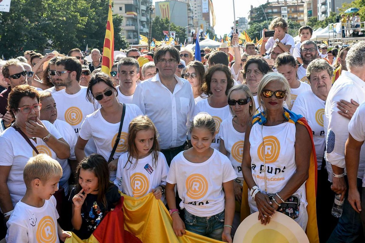 People pose with the president of the Catalan regional Government, Carles Puigdemont (centre), during a pro-independence demonstration, on Sept 11, 2016, in Barcelona during the National Day of Catalonia.