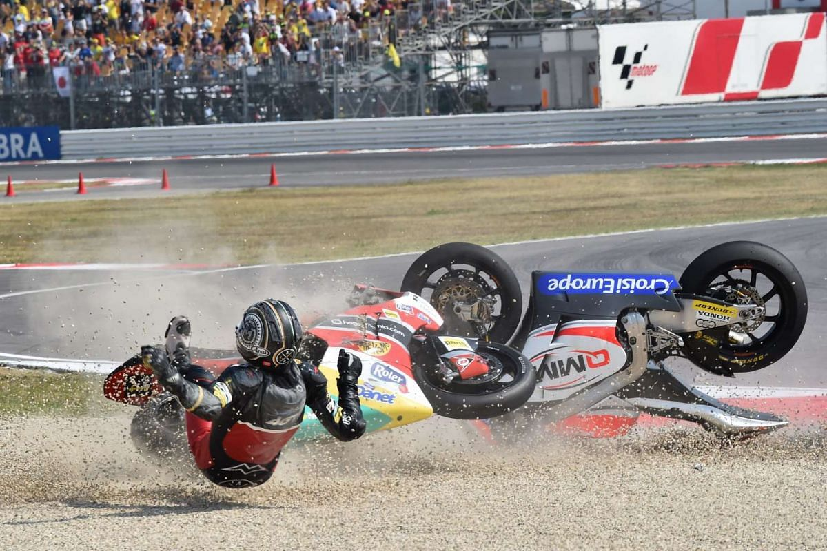 AGR Team Moto2 Spanish rider Alex Pons falls, along with QMMF Racing team Belgiqn rider Xavier Simeon (unseen), during the Moto2 race of the San Marino Moto GP Grand Prix at the Marco Simoncelli Circuit in Misano, on Sept 11, 2016.