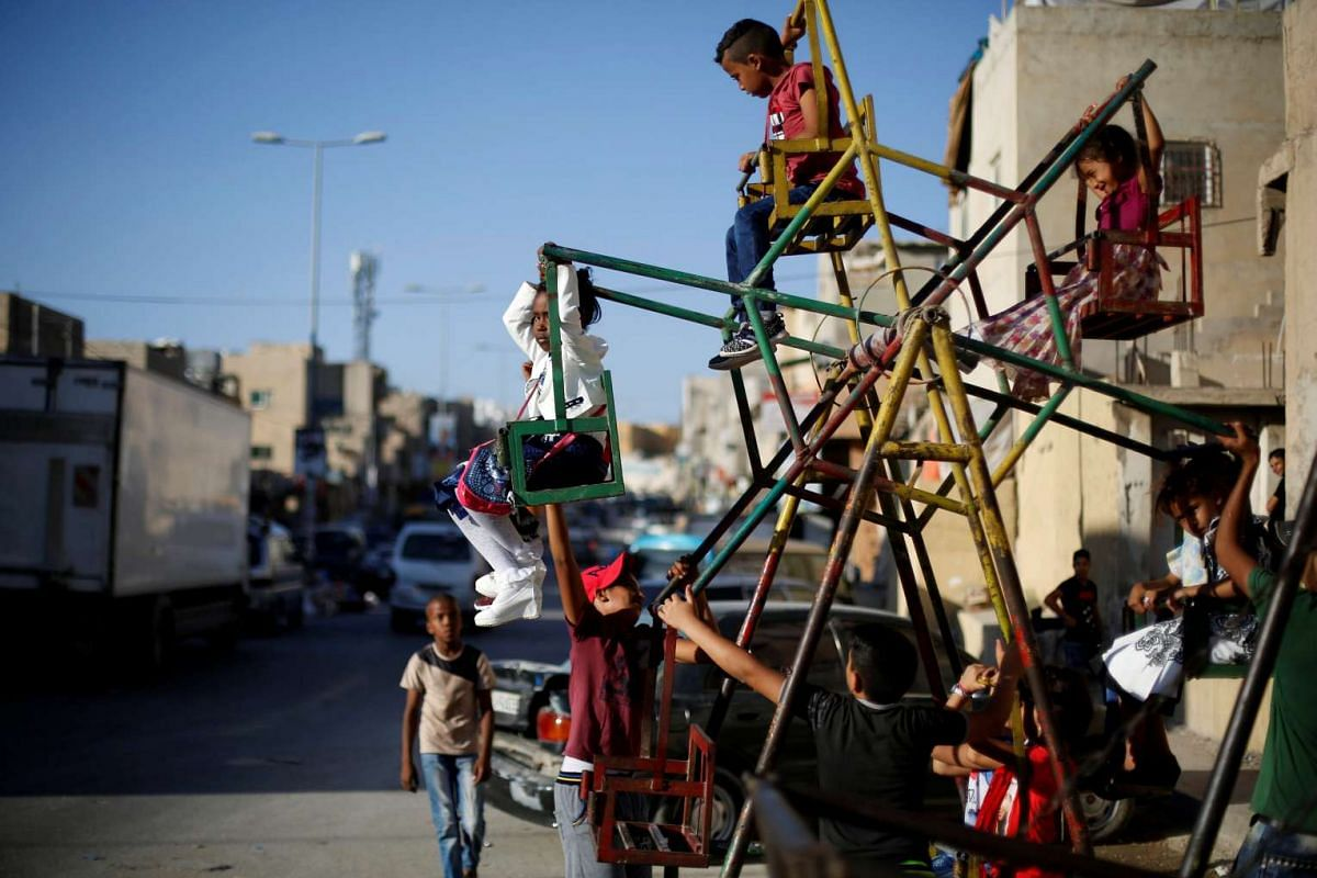 Palestinian children play on a mini ferris wheel on the first day of the Muslim holiday Eid al-Adha at Al-Baqaa Palestinian refugee camp near Amman, Jordan, on Sept 12, 2016.