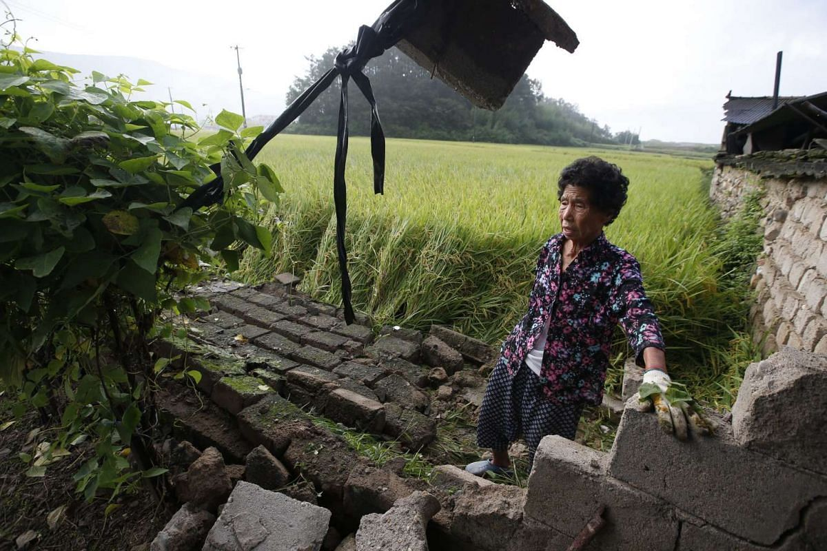 A South Korean earthquake victim stands by her damaged house on Sept 13, 2016, following a 5.8 magnitude earthquake a day earlier in Gyeongju-city, Gyeongsangbuk-do.