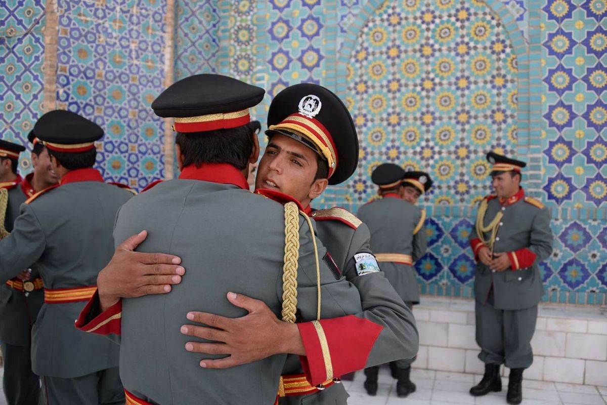 Members of an Afghan guard of honour greet each other after offering Eid-al-Adha prayers at the Hazrat-i- Ali shrine in Mazar-i Sharif on Sept 12, 2016.