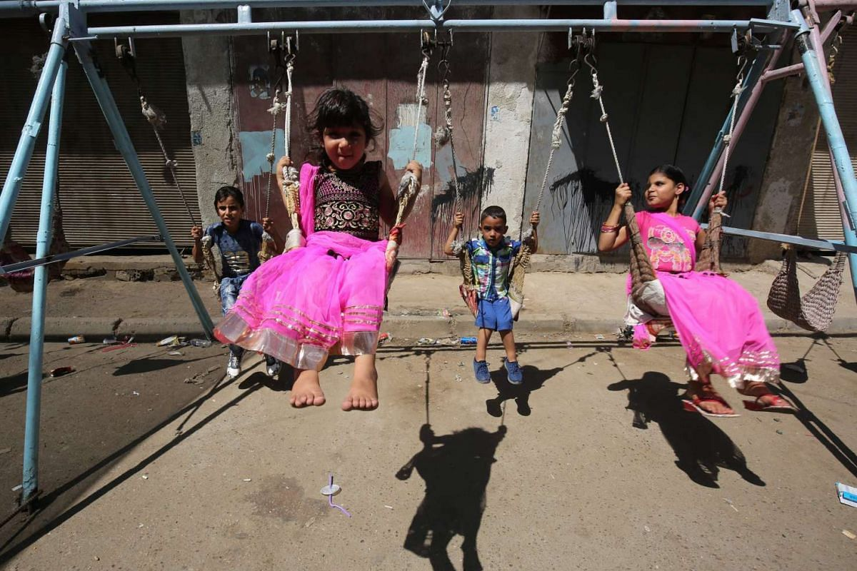 Iraqi children play on a street in the capital Baghdad on the first day of Eid al-Adha holiday, on Sept 12, 2016.