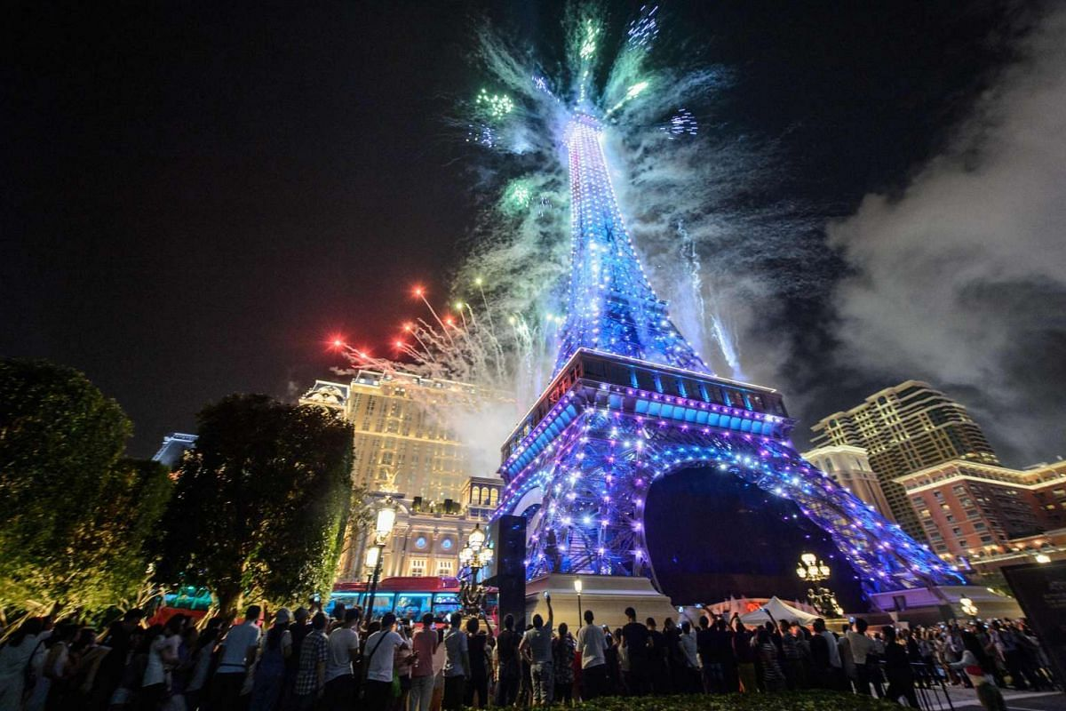 People gather to watch fireworks exploding from a replica of the Eiffel Tower after the opening of the Sands new mega resort The Parisian in Macau, on September 13, 2016.